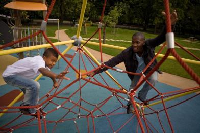 teenager and father on climbing frame